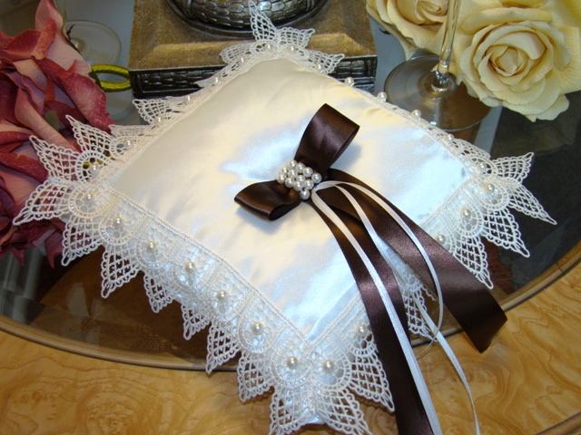 "Candlelight Lace   Pillow  Ivory silk taffeta framed with a 2 1/4"" ivory lace, highlighted with an embellishment of 6mm ivory pearls.  A brown satin ribbon  3/4"" wide centered with 3 rows of pearls gives this pillow the finishing touch. The hand ribbon sewn to onto the back of pillow will assist tiny hands during the ceremony. Measures approx. 8 x 8 inches."