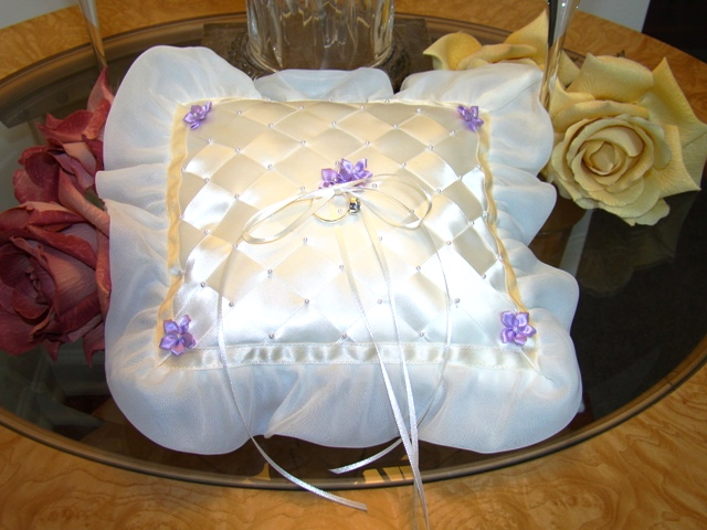 Ivory Lattice Pillow  This ring bearer's pillow is a one of a kind heirloom piece.  Hand woven ivory ribbons over silk taffeta, embellished with white pearls and lavender orchids make this a truly collectibale piece. Two sets of narrow ribbons will secure the rings and a hand ribbon sewn onto the back of the pillow will assist tiny hands during the ceremony. Measures approx. 8 x 8 inches