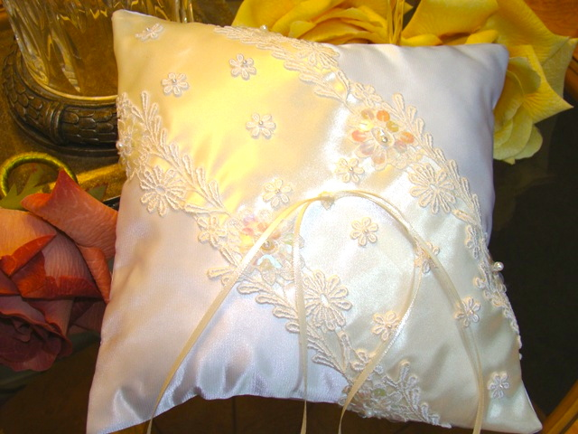 "Heavenly Lace  This uniquely crafted pillow is one of a kind. Sequenced lace hand stiched onto 4 1/2"" wide ivory satin ribbon over white satin base and enhanced with white daisies secured with 2mm white pearls. Hand ribbon on back will allow for easy handling during ceremony. Measures approx. 8 x 8 inches"