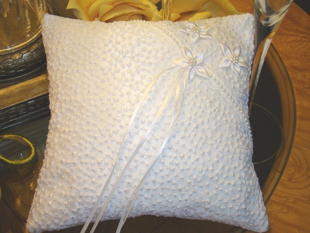 """White Dream Pillow  Exceptional one of a kind. White dotted tulle over satin festooned with beaded lace and skillfully completed with three beaded flowers. The set of narrow ribbons will hold your rings and the hand ribbon on back of pillow will allow for easy handling. Measures approx. 8"""" x 8"""""""