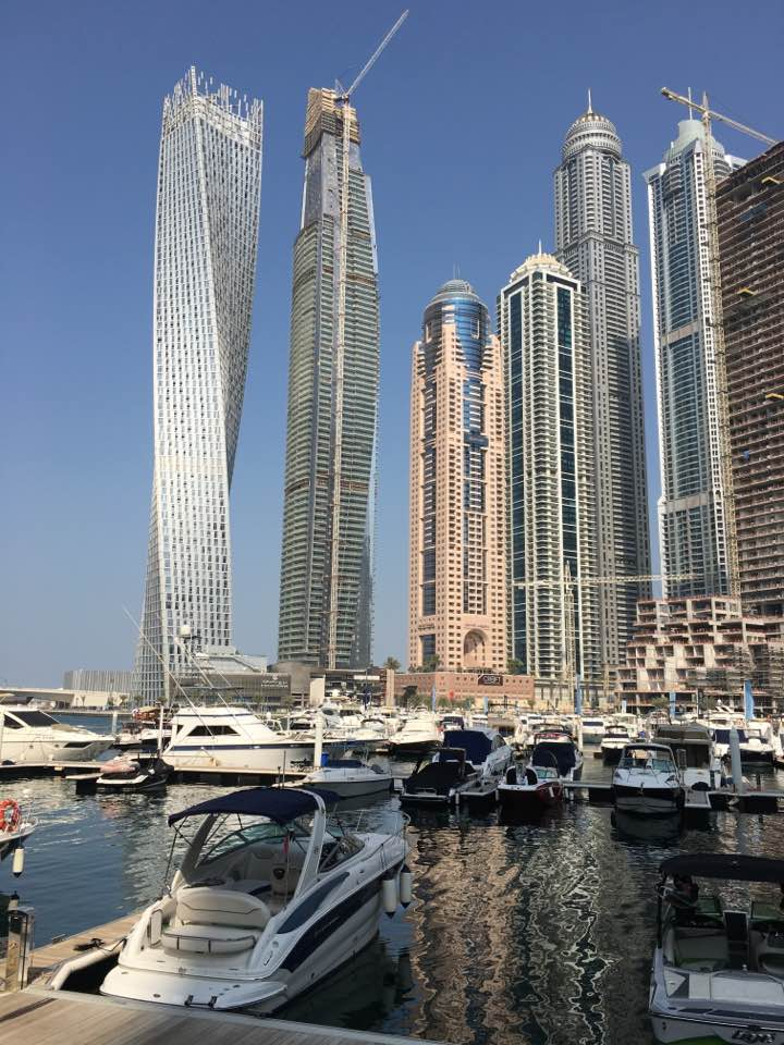 A man-made marina in Dubai is surrounded by 100 story condo towers