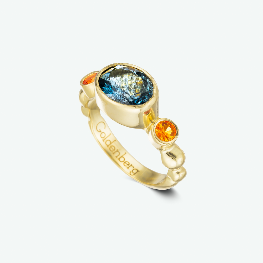 'Family heirloom project' This lovely ring is composed of 18k yellow gold and set at its center with a beautifully rare reutilized aquamarine and orange sapphires on the sides.