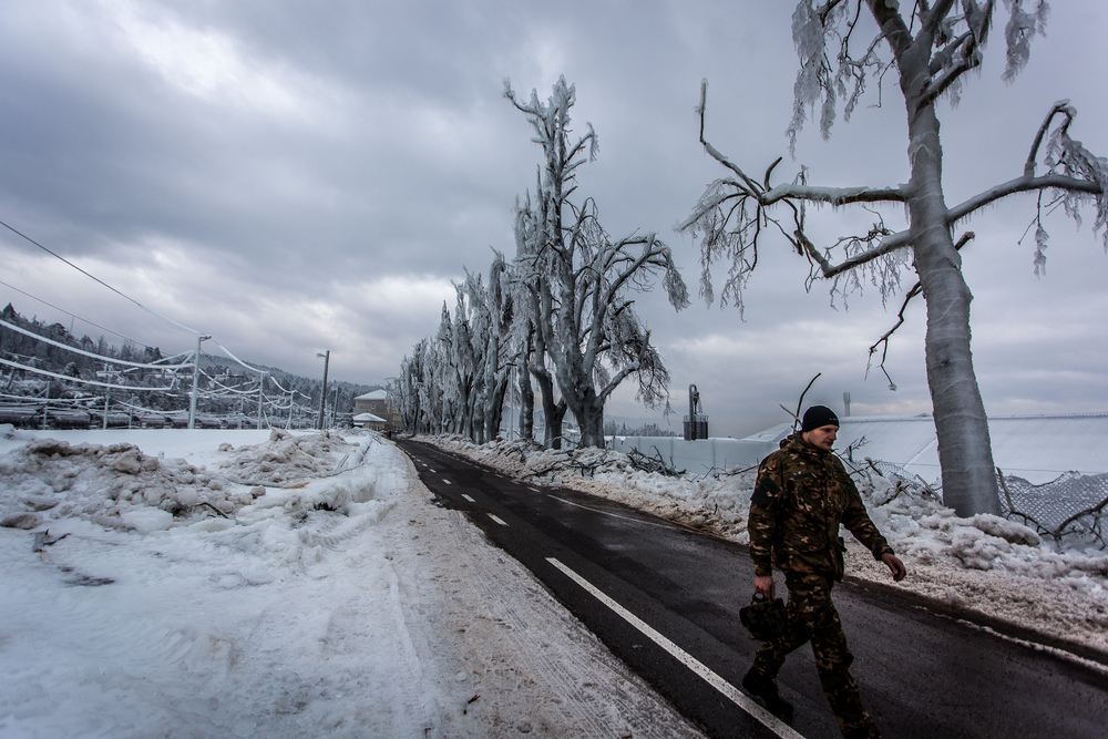 Member of the Slovenian Armed Forces walking through a frozen avenue from train station to the city centre