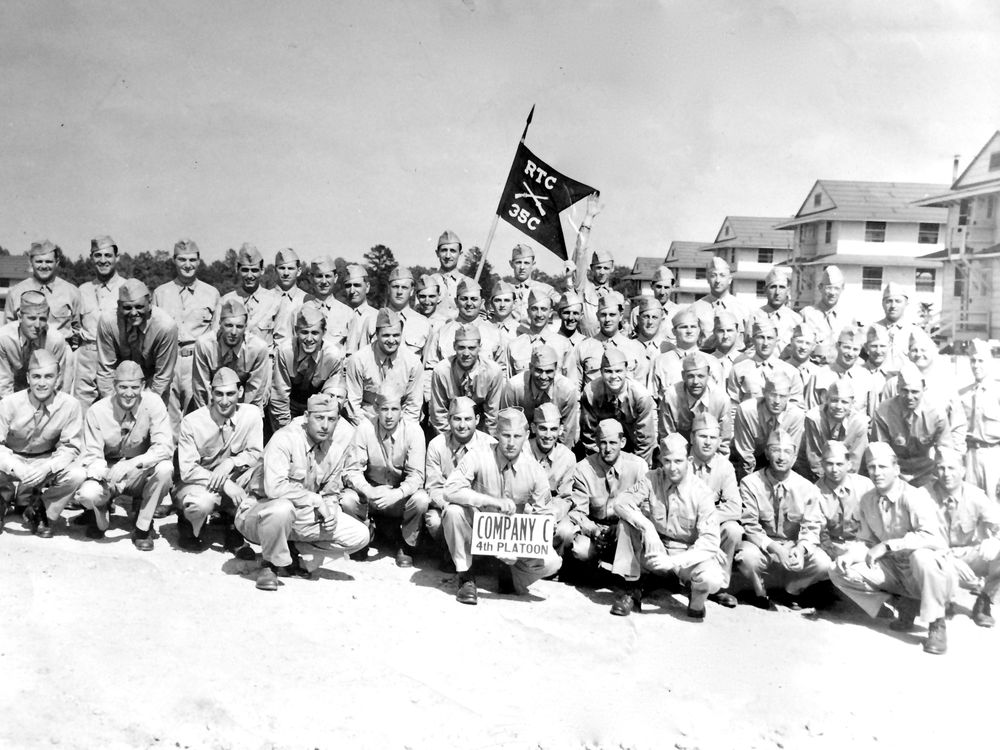 My grandfather can be seen in the back row, his arm up, holding the flag.