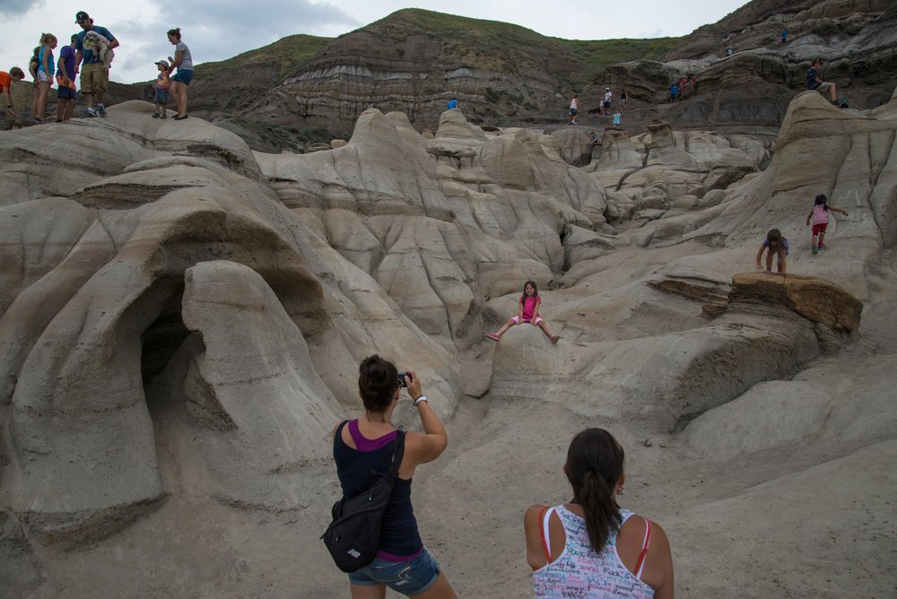 "Kids are playing on hoodoos near Drumheller, Alberta. The word hoodoos comes from the Hausa language of West Africa for hu'du'ba, which means to ""arouse resentment produce retribution."""