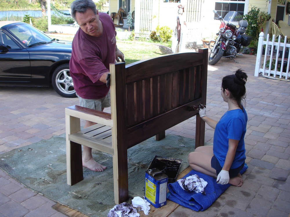 Doug and Paige staining custom built outdoor furniture