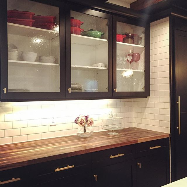 Gorgeous and eclectic mix of traditional shaker cabinets and modern brushed brass hardware. #brushedbrass #blackcabinets #subwaytile #glasscabinets #lecrueset #lewisdolin #seedyglass #glassdoors #kitchenrenovation #dallasdreamkitchen #dallaskitchen #dallasrenovation #dfwconstruction #dfwcontractor #contractorsofinsta #kitchenreno #dallasconstruction #dallaskitchenremodel #blackandwhitekitchen #walnutcountertops #butcherblockcountertop
