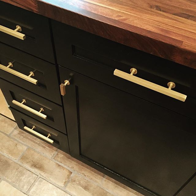 Brushed Brass Lews hardware goes in on our black satin cabinets! #brushedbrass #dallasrenovation #dallaskitchen #butcherblock #walnut #lewshardware #blackcabinets #shakercabinets #blackkitchen #brickveneer #brickfloor #blacksatin #kitchendesign