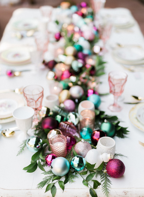 Colourful votive holders and tree ornaments set on a green garland, bringing the tree to the table. Photographer:  Jennifer Fujikawa Photography  Design:  Seven Stems