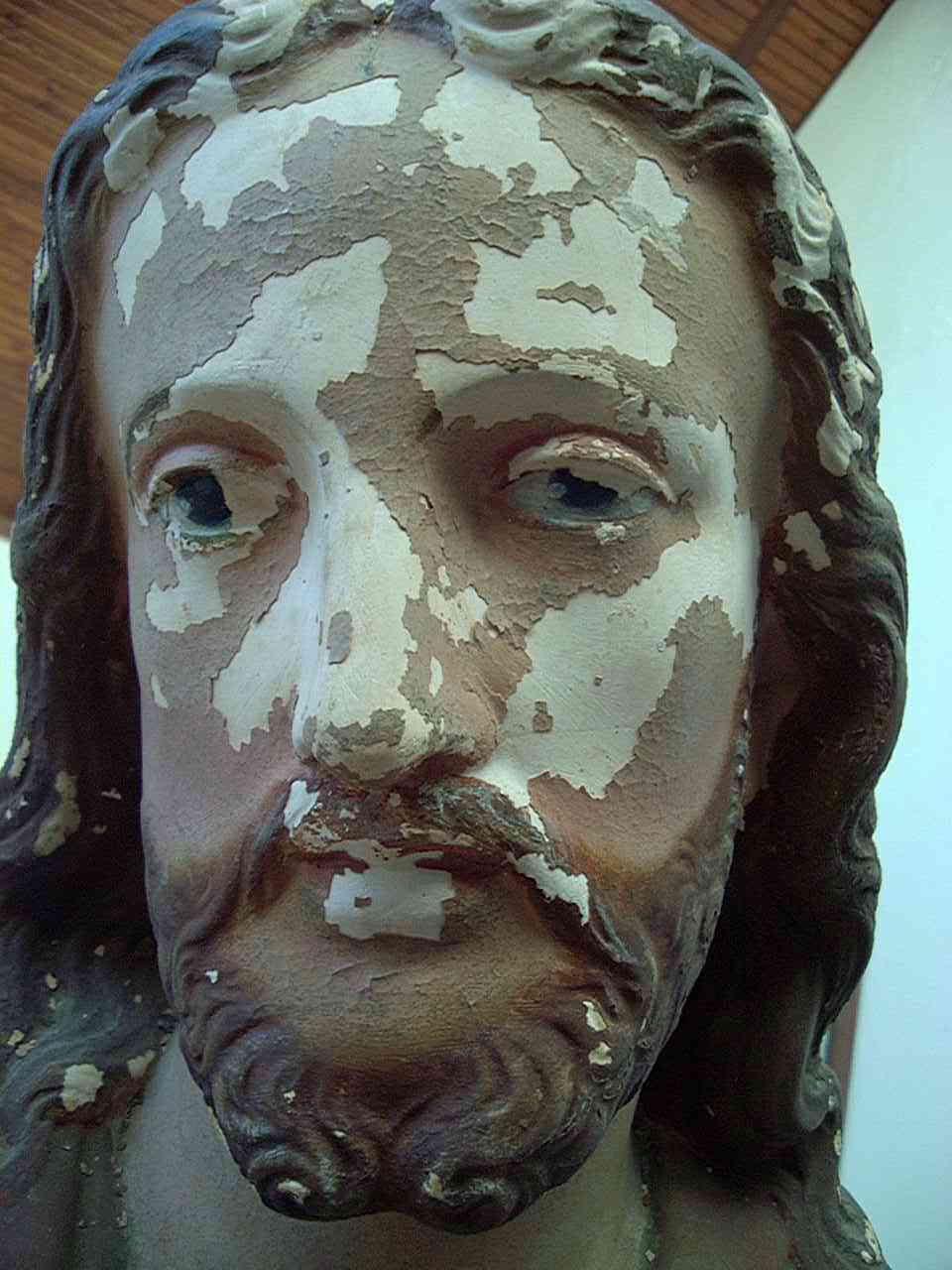 "Detail: Damaged head / face of plaster statue ""Sacred Heart of Jesus"""