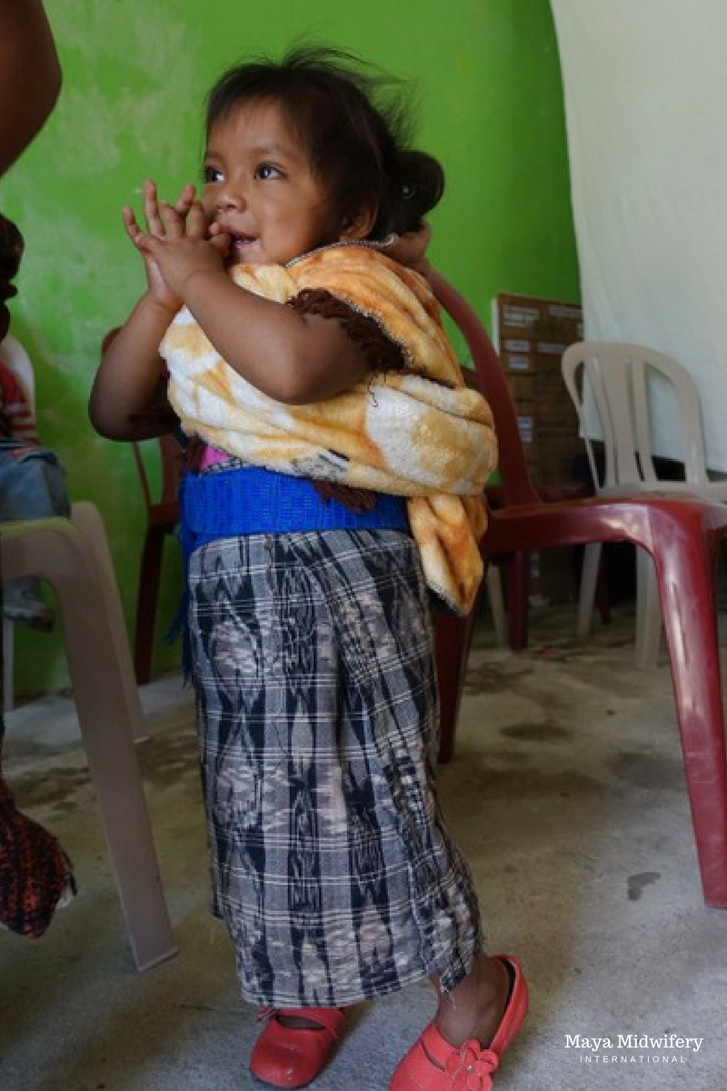 Ana's firstborn child waits patiently during her mother's appointment at the mobile clinic.