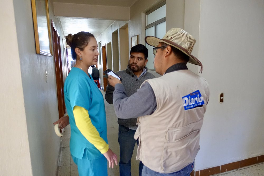 A reporter from Nuestro Diario interviewing Dr. Valeria about the clinic at ACAM