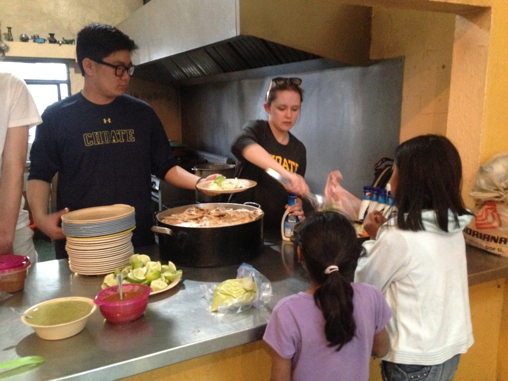 YJ (left) and Choate schoolmate Nicole serve the children for a Sunday night dinner at Casa Hogar!