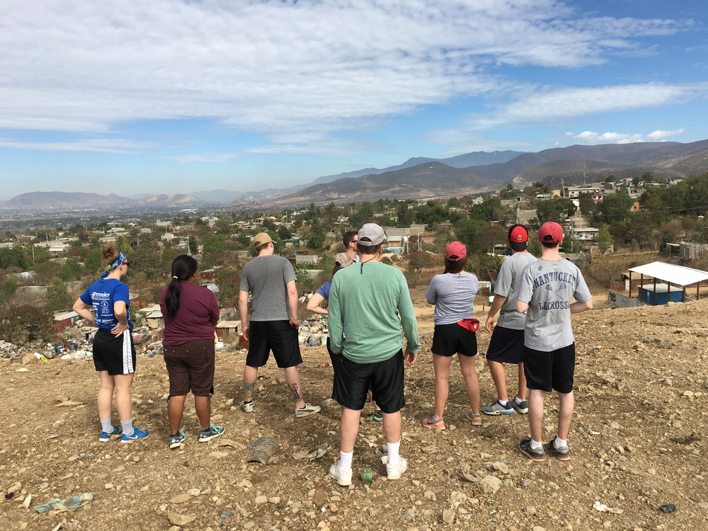 The Sacred Heart University group gets a tour of the Oaxaca City garbage dump from Simply Smiles staffers Gaby and Zach, while standing on one of the trash mountains that overlook the communities below. (January 2016)
