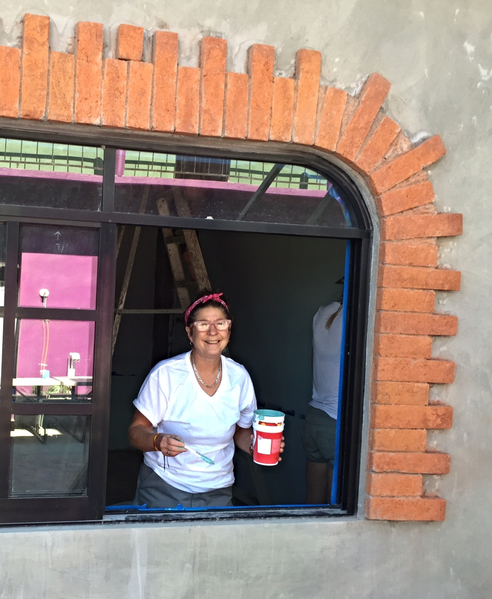 Michele is all smiles as she paints the space that will soon be the kitchen at our children's home!