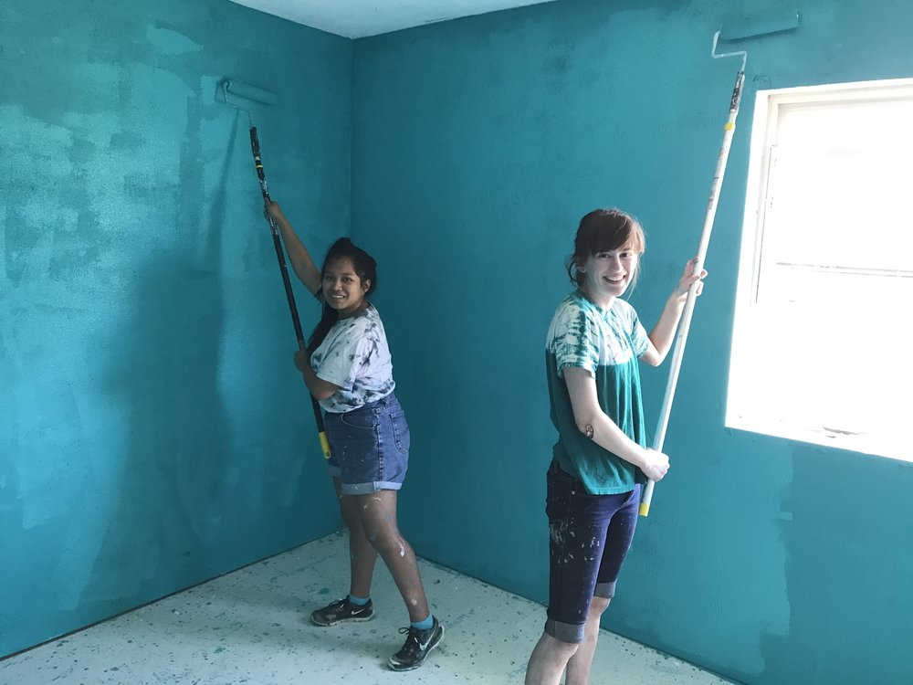 Volunteers Siona and Ruby work on painting the inside of a newly-renovated home of a community member.