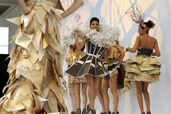 Models present dresses made with recycled office files at the CeBIT computer fair in Hanover March 2, 2010. REUTERS/Christian Charisius