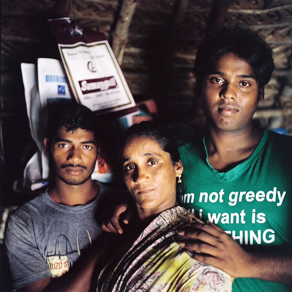 Lakshaya (far right) poses with her mother and brother in their house in Devenappatinam. Laksheaya's family are very supportive of her kothi identity. Her brother often hangs out with she her kothi friends. Mohana and Lakshaya are best friends   and confidantes. November 2013.