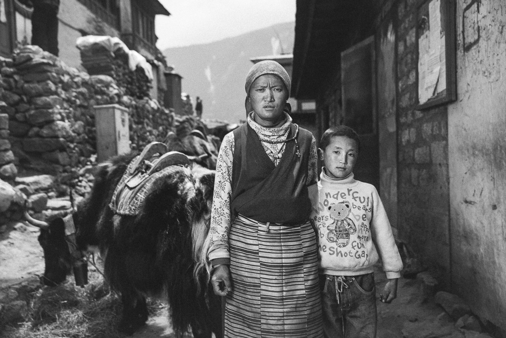 Ang Nimi lost her husband Dorji in the April 18th, 2014 Everest ice fall avalanche. She's pictured here with one of their four children, son Lhakpa Tshering.  Photo: Grayson Schaffer
