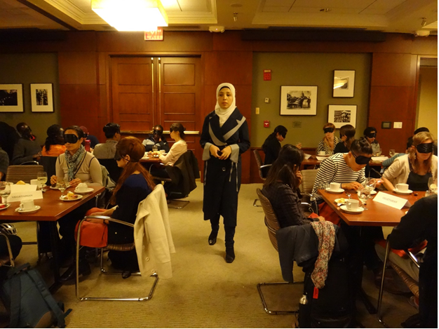 Sara Minkara (President and Founder of ETI) hosting a dining in the dark event with a room full of Harvard Kennedy School of Government students (April 10, 2014).