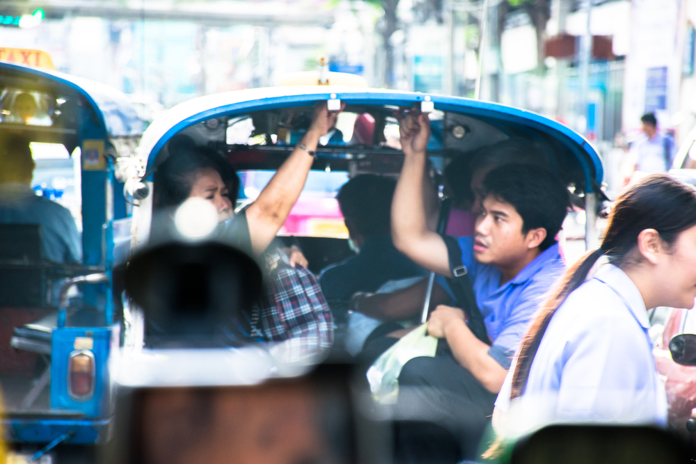 "People packed at the back of a ""tuk-tuk"" in traffic. Tuk-tuk is an essential part of the daily life in Bangkok."