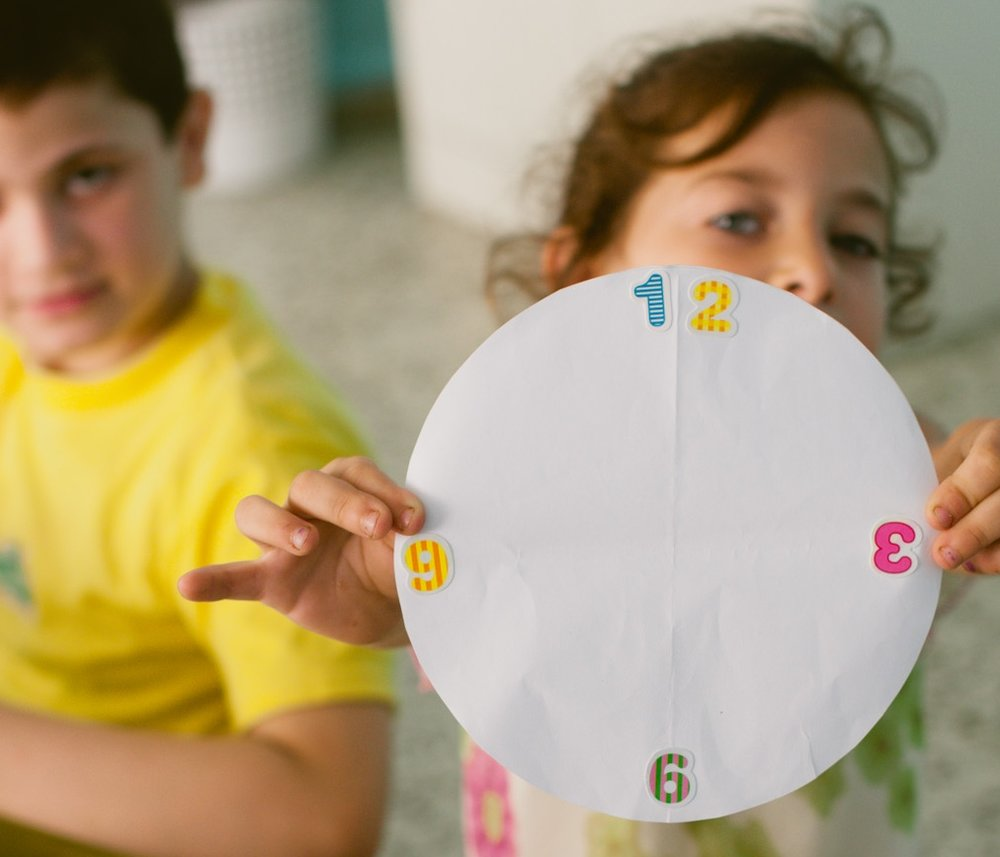 A girl displays her art project, which resembles a clock, while a boy in the left background looks on.