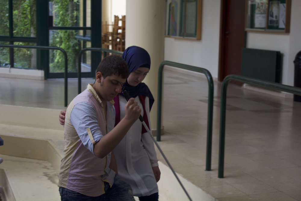 In the picture: a male Life Skill Program participant learns to use a white cane at the University of Balamand while walking with a female guide.