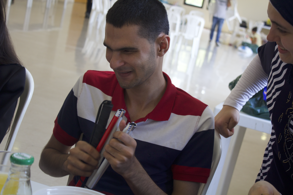 In the picture: a Life Skill Program participant feels the tip of a white cane.