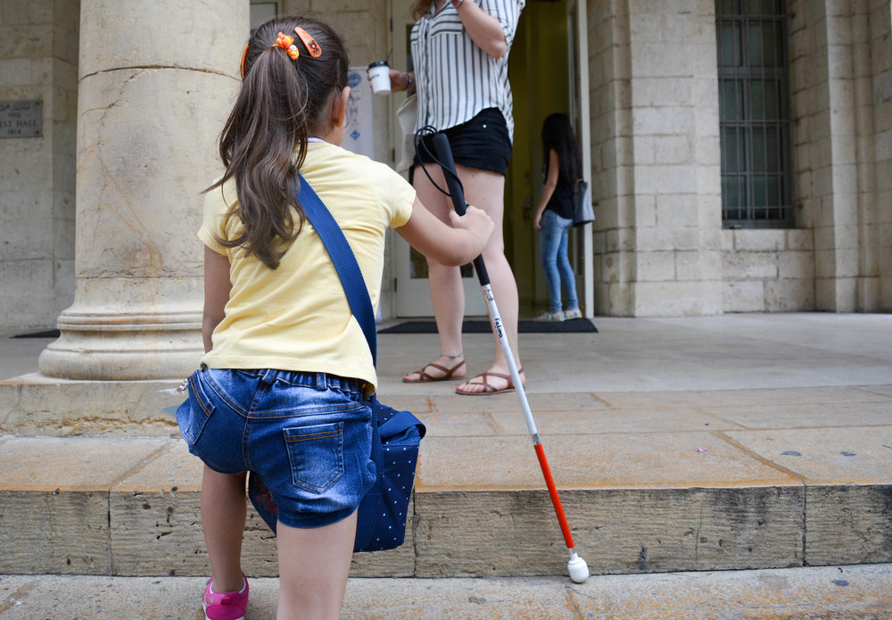 In this photo: A young girl uses a white cane to walk up the stairs