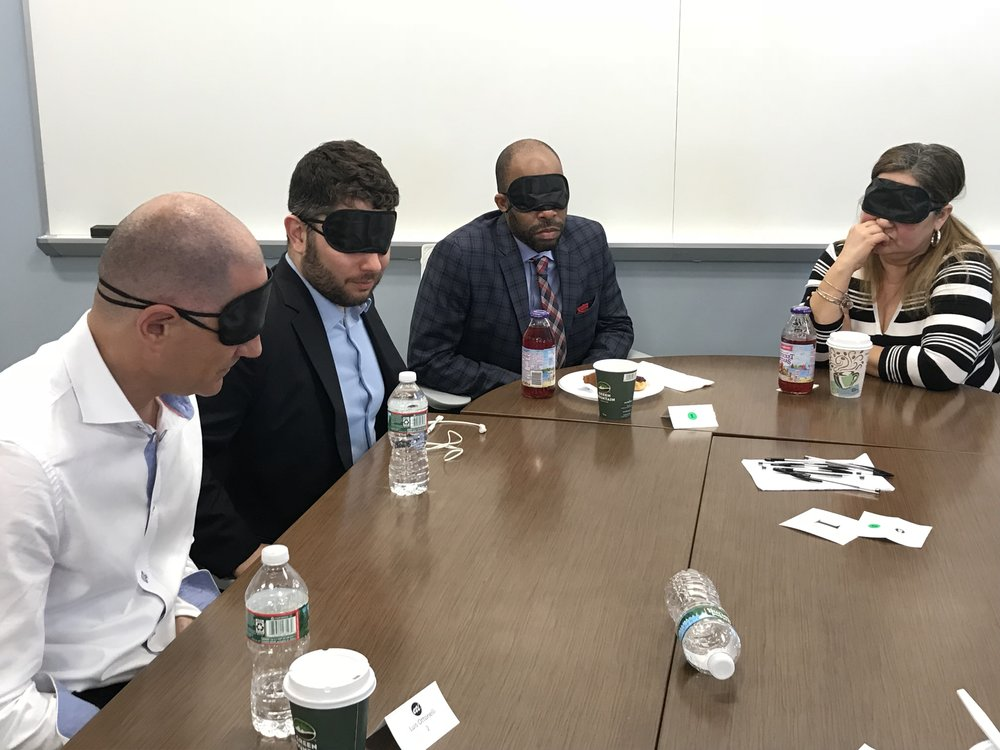 In this photo: Four blindfolded Teambuilding in the Dark participants listen to a speaker out of frame