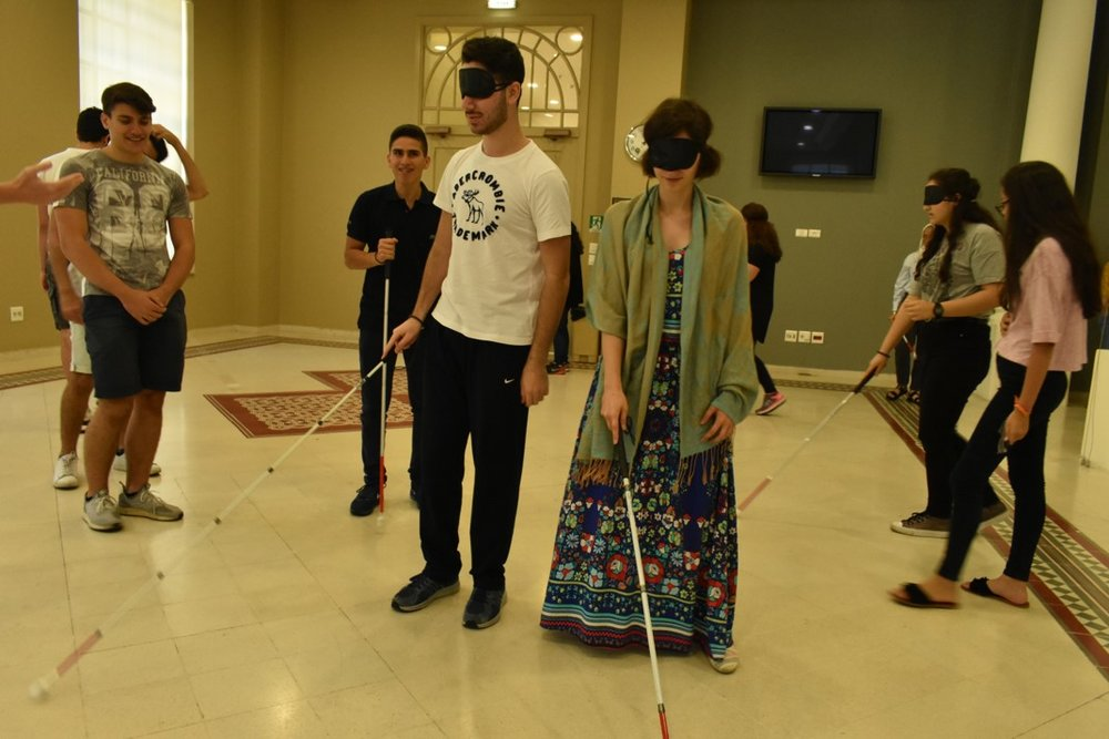 Blindfolded volunteers practicing how to use the white cane