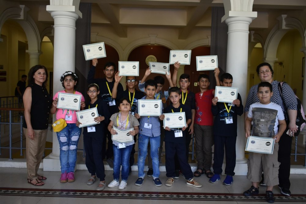 Visually impaired participants from group yellow (ages 11 to 14) showing their certificates of participation, with Anna Barbosa, Edith Bitar from US Embassy, and volunteers