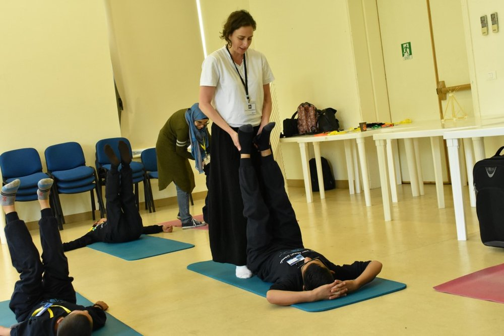 Visually impaired participants on yoga mats receiving instruction on yoga technique