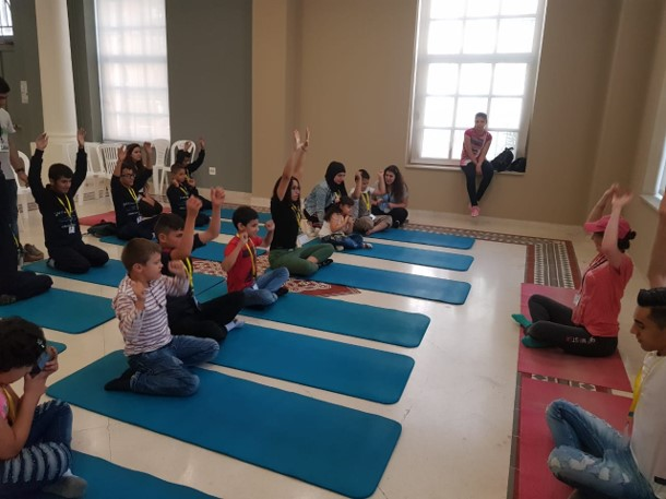 Visually impaired participants sitting on yoga mats facing yoga instructor