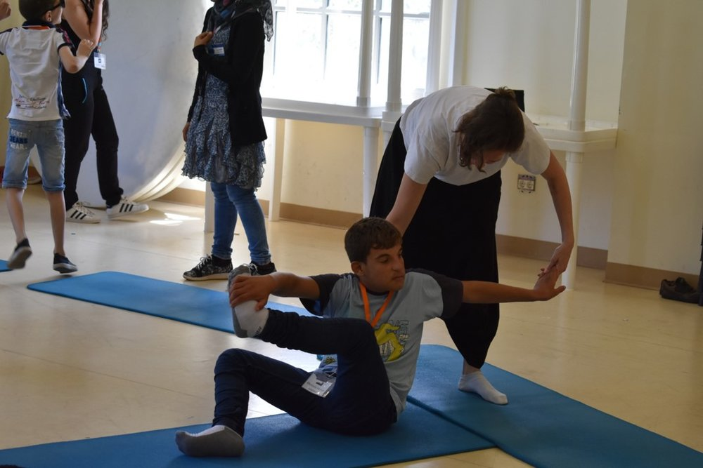 Yoga instructor assisting visually impaired participant with his yoga pose
