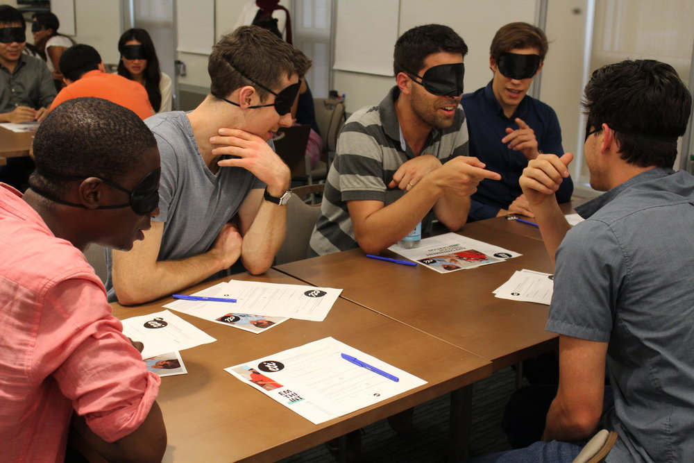 Five blindfolded MBA candidates are engaged in an active conversation around their table, smiling and gesturing at each other.