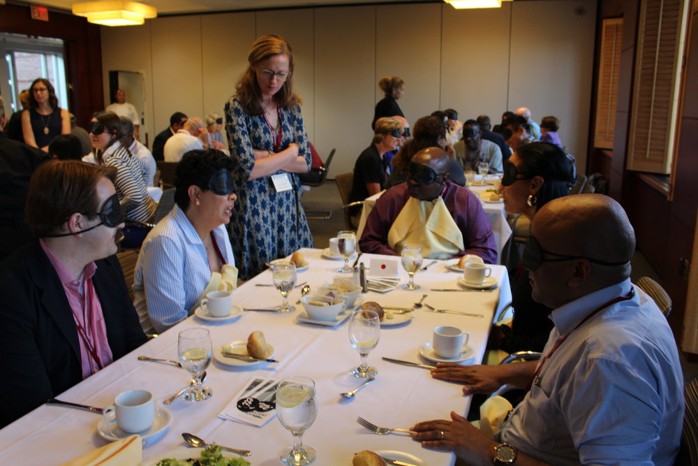 Five blindfolded participants engage in a discussion at their table while a program director stands next to them and listens.
