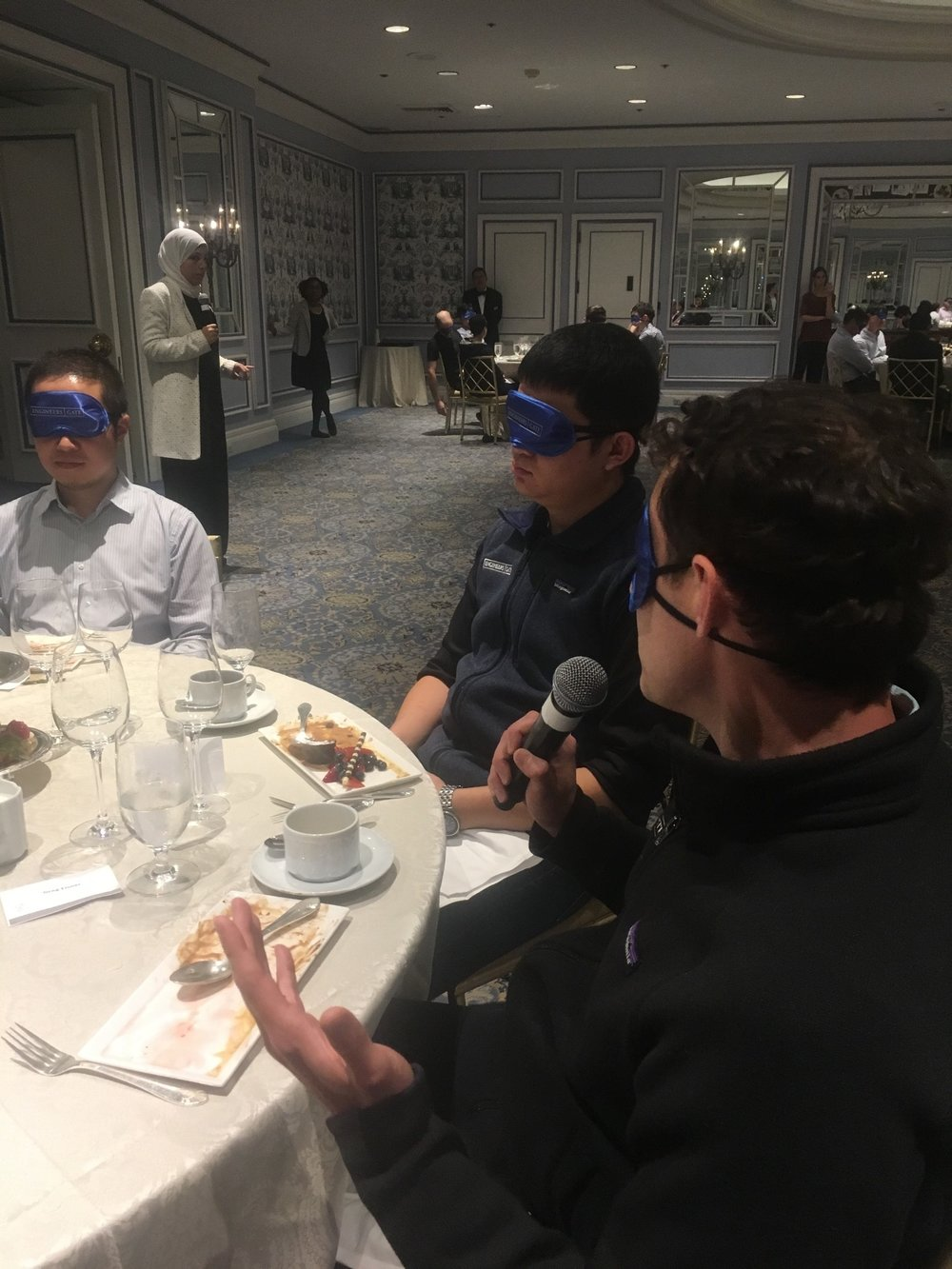 Blindfolded man speaking at a table while other blindfolded participants are listening intently