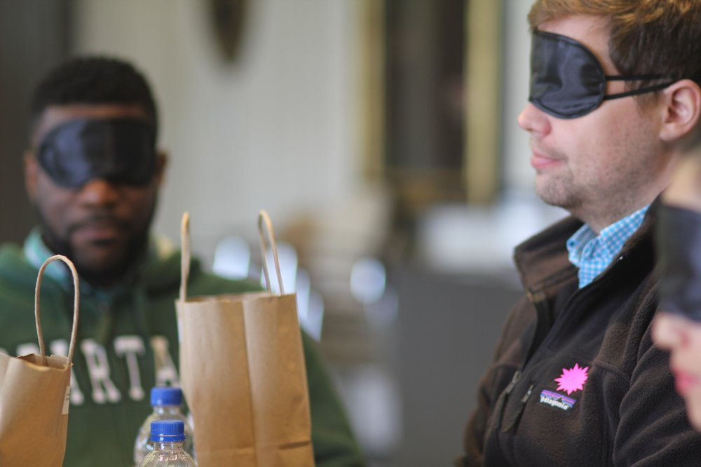 Two blindfolded participants listening intently to the facilitator's instructions