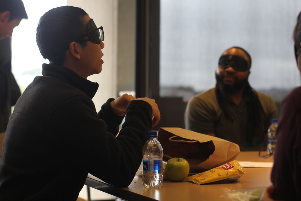 A blindfolded participant leading the conversation while a group of other blindfolded participants listen