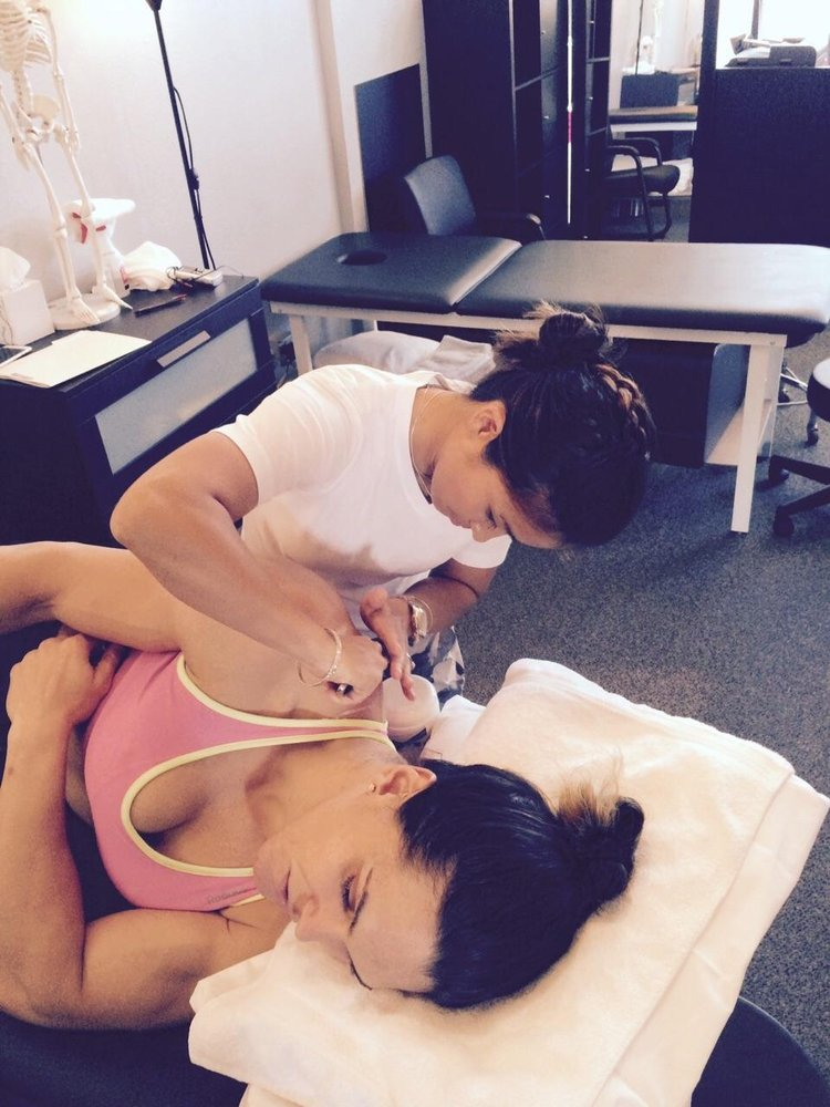 Dr. Su providing Instrument Assisted Soft Tissue Mobilization to MMA fighter Gabi Garcia.