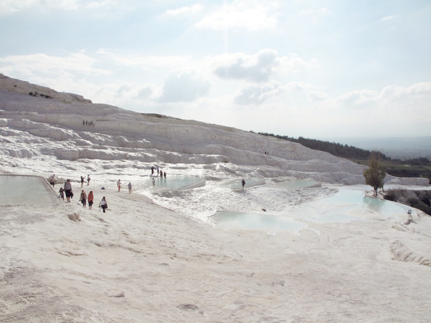 """Like something from another world, Pamukkale, meaning """"cotton castle"""" in turkish, is a natural site in denizli province in southwestern  t urkey. The city contains hot springs and travertines.flowing water leaves  terraces of carbonate minerals that people have been bathing in for thousands of years."""