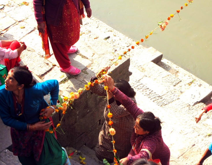 There wasa beautiful sense of community and team work here as the women hurry around to put up lovely strings of marigold flowers across the holy river.