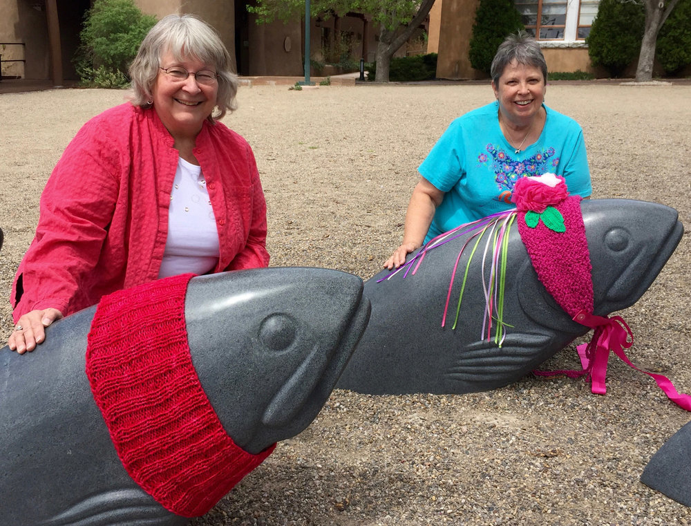 Kathy Konecki and Janet Reffert with their fiber bombed fish at the Convention Center.