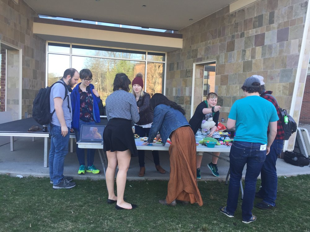 Image description: Students at Skidmore College gathered around a table of stim toys and autism acceptance materials.