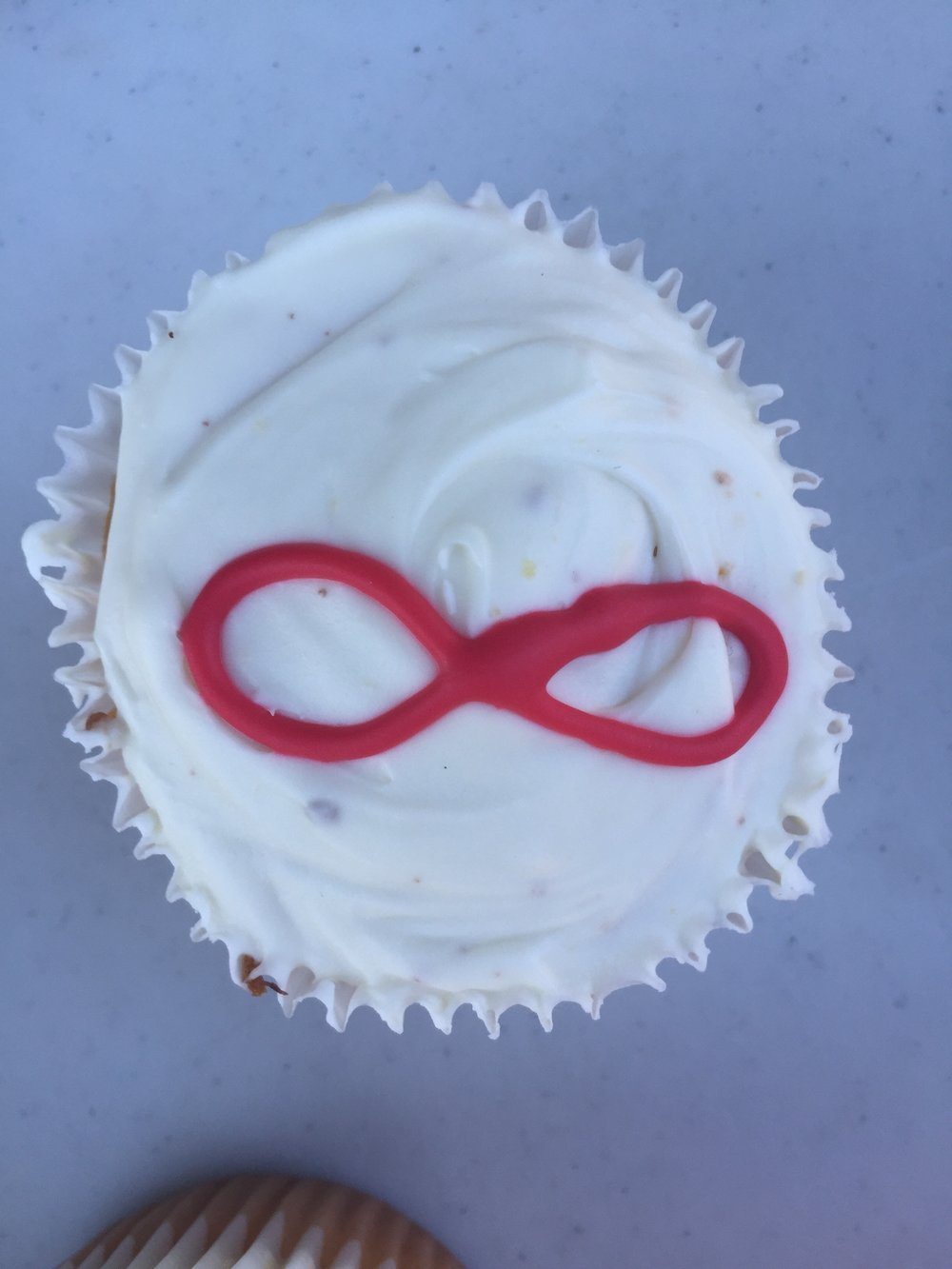 Image description: A cupcake with white frosting and a red infinity symbol in the center.