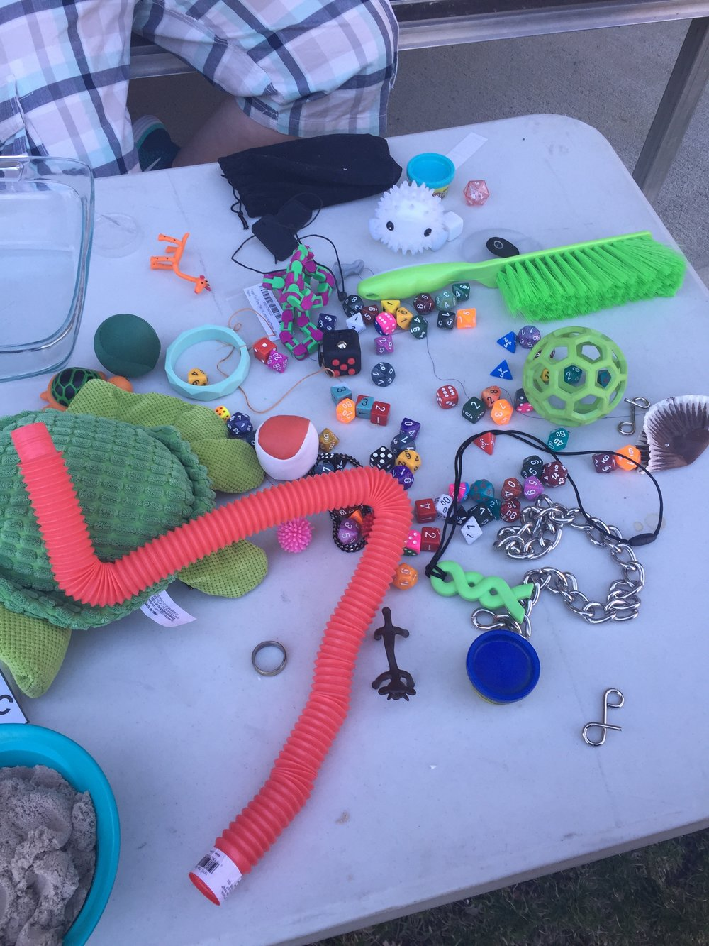 Image description: A table displaying many types of stim toys including fidgets, a sensory brush,chewables, jewelry and plushies.