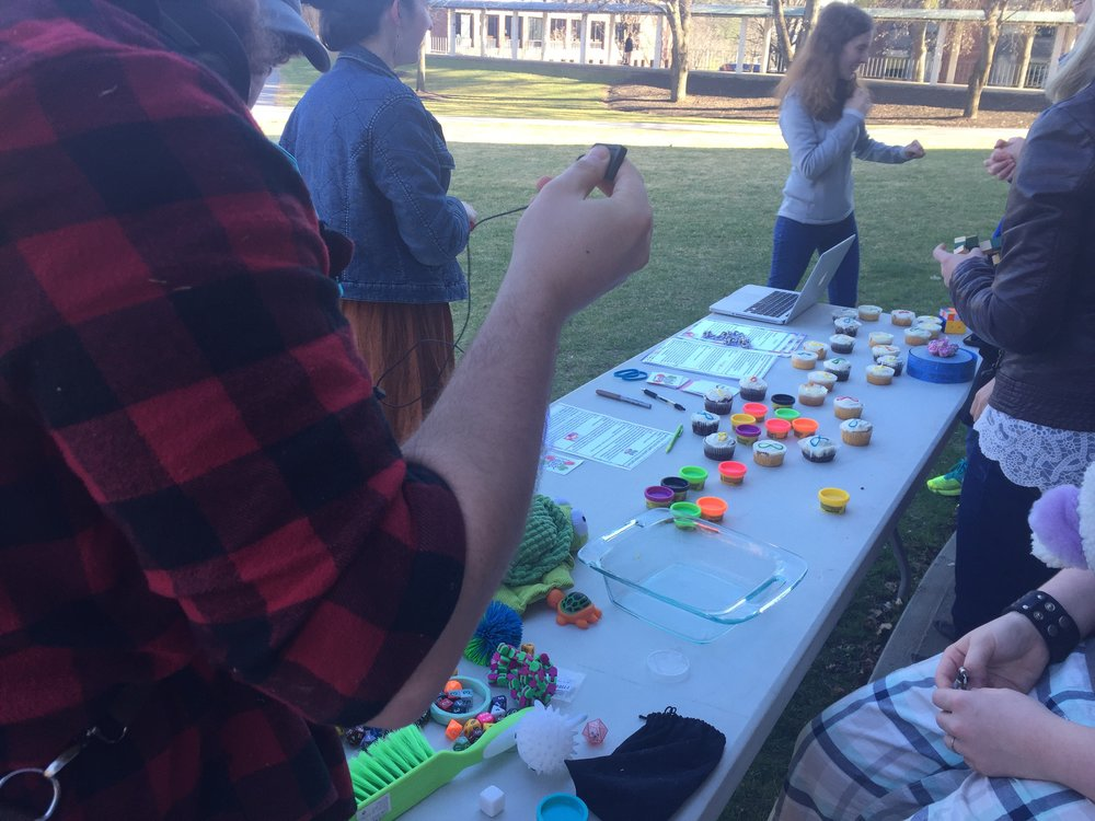 Image description: Cropped view of people standing at a table displaying autism acceptance materials, mini tins of Play-do, cupcakes and stim toys.