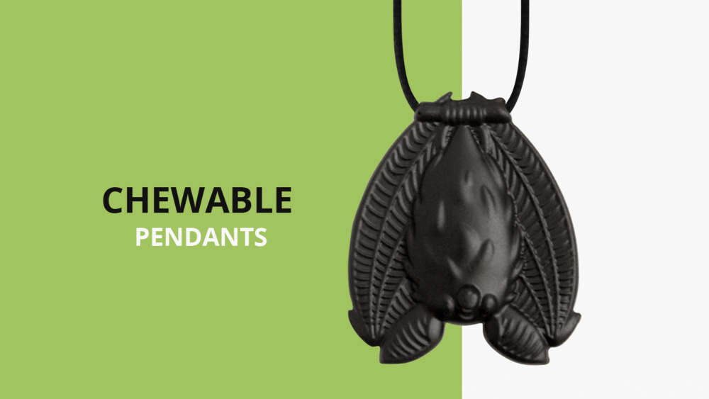 A photo of a black chewable bat pendant necklace, hanging upside down by its feet from the necklace cord. It says chewable pendants.