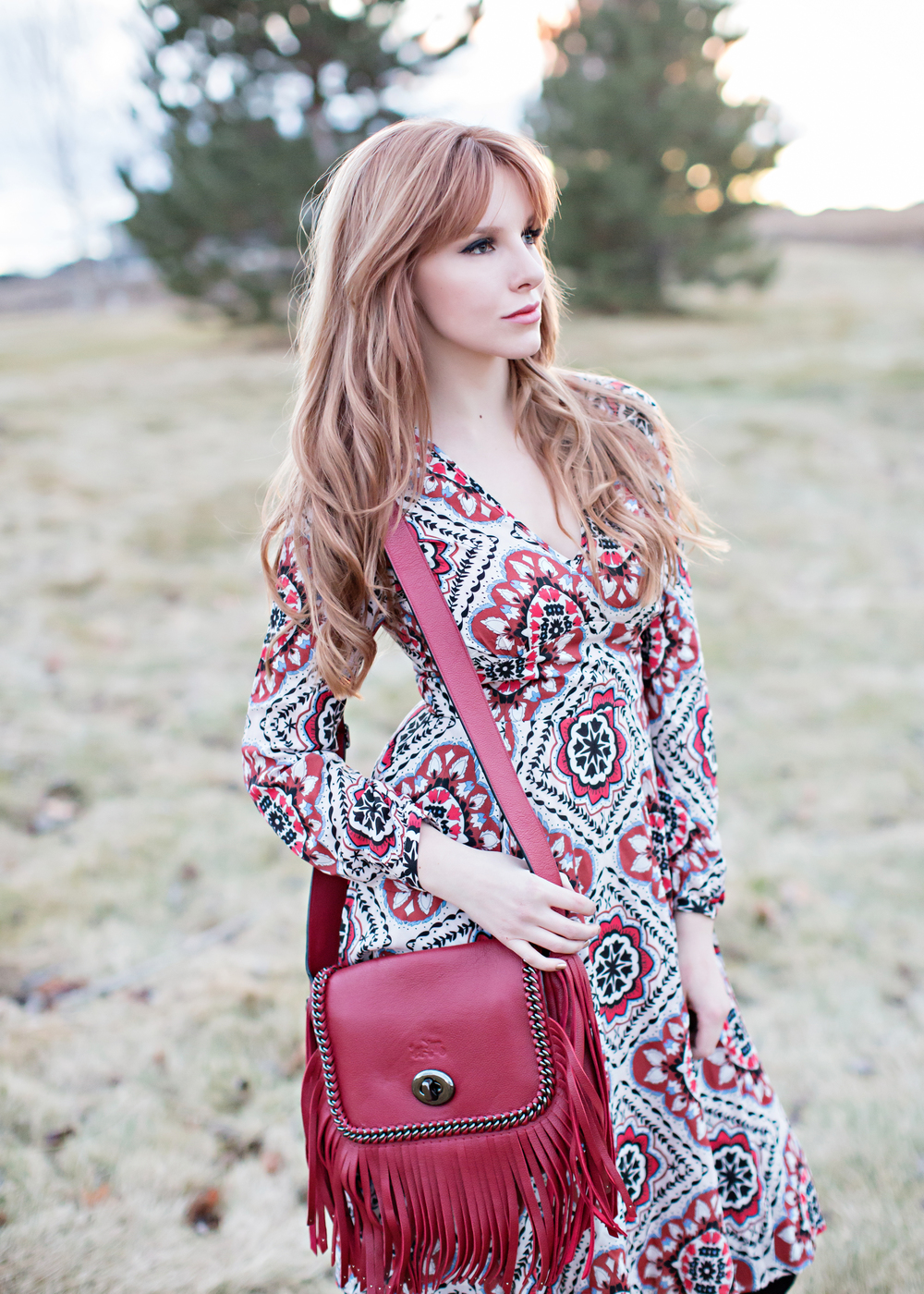 Red head wearing yumi kim dress, red fringe bag, 70s style